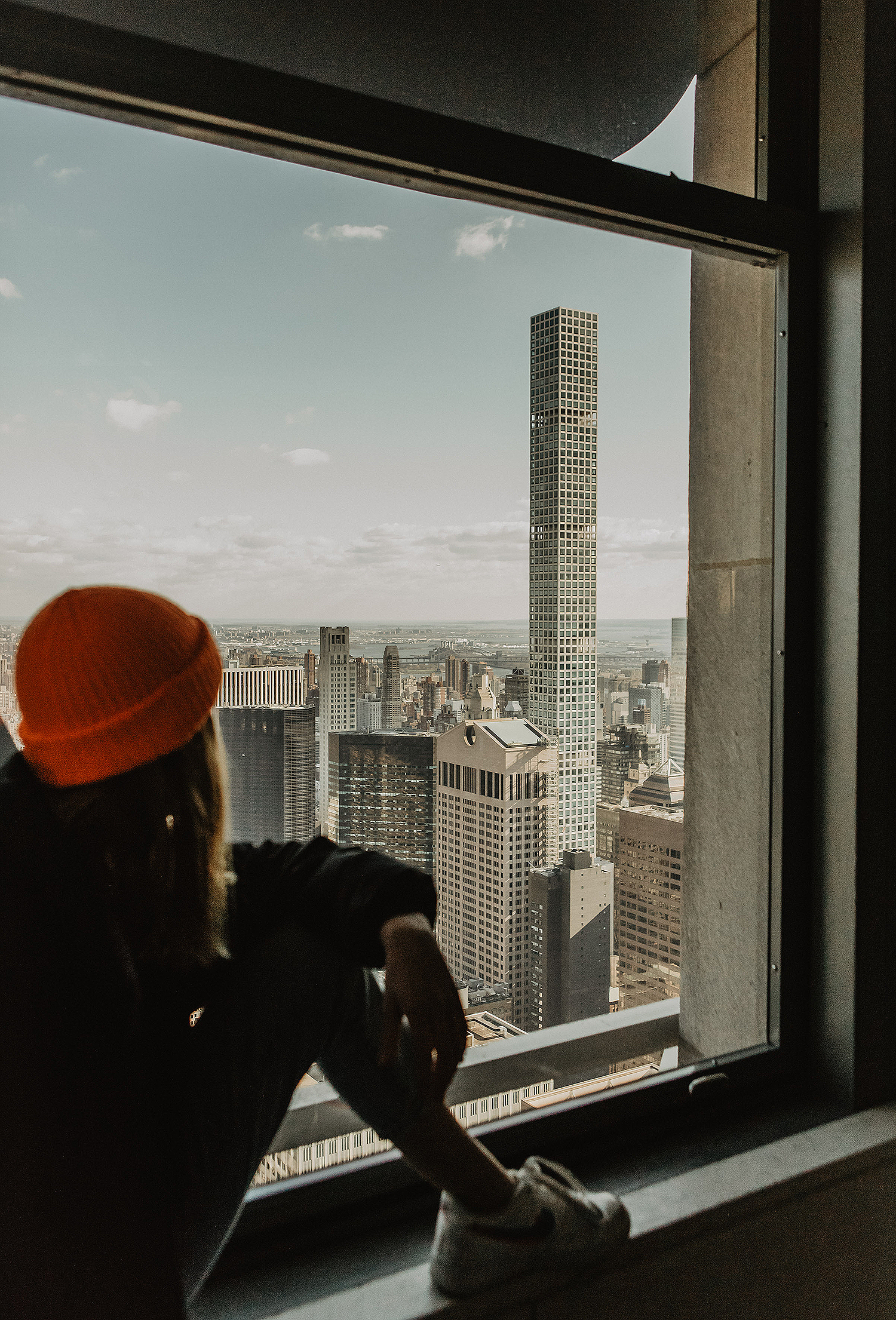 girl looking from window to manhattan