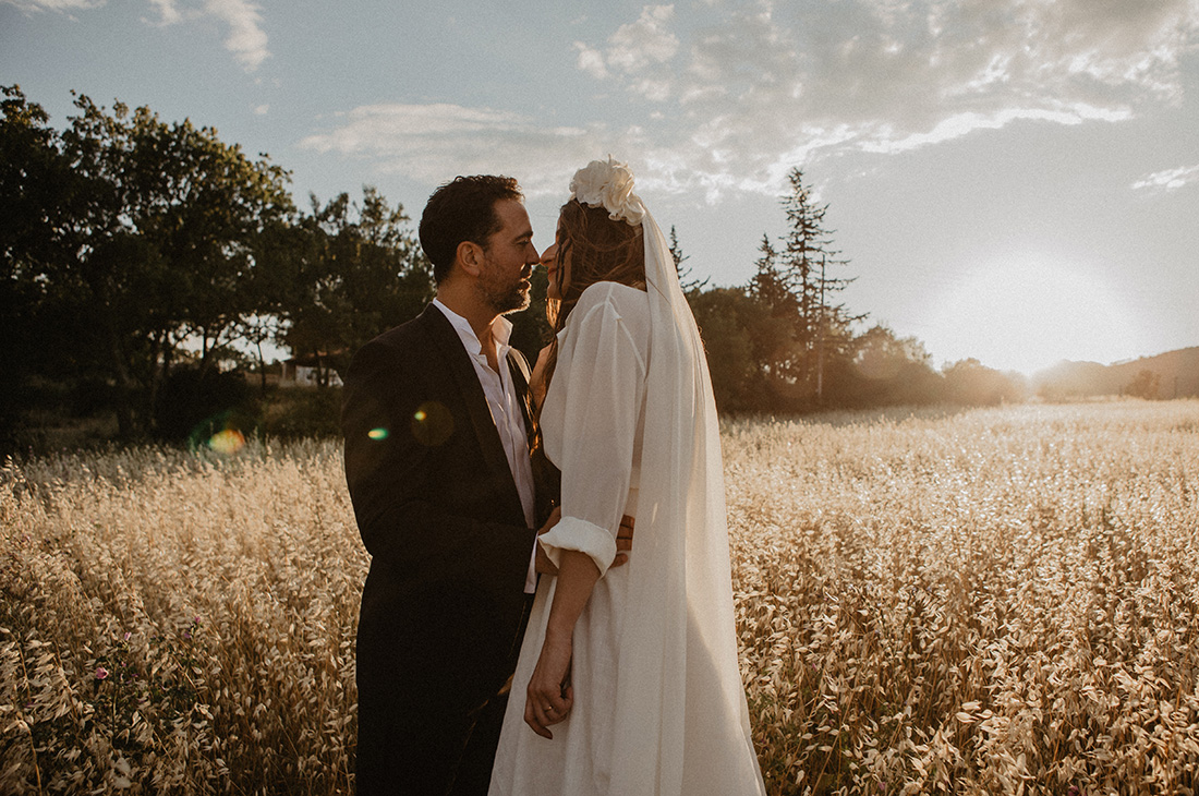 couple kissing on their wedding day in a sunset field